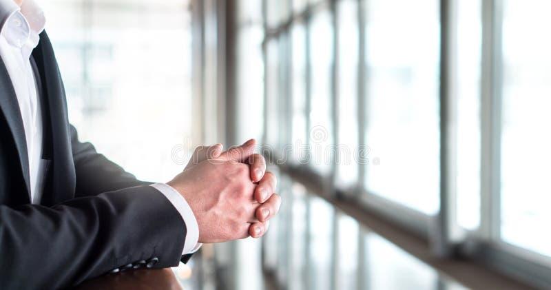 Bedrijfs en mens die uit het venster denken kijken stock fotografie