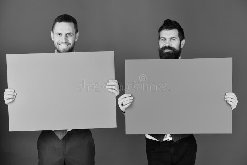 Bedrijfs en presentatieconcept Reclame of commerciële affiches De mensen met baarden houden raad op blauwe achtergrond royalty-vrije stock fotografie