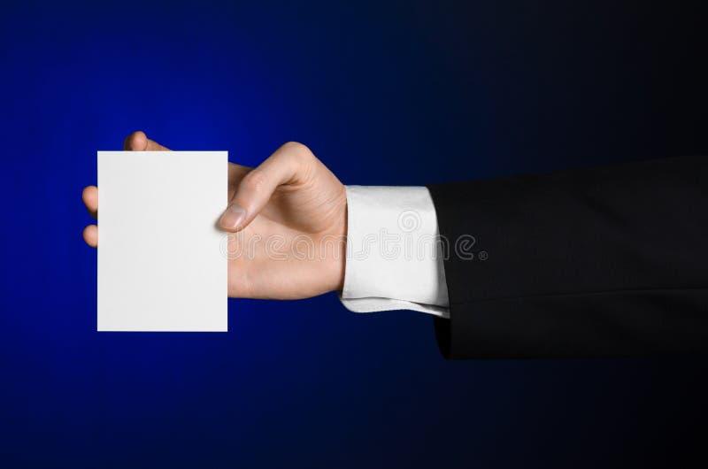 Bedrijfs en reclameonderwerp: Mens die in zwart kostuum een witte lege kaart in zijn hand op een donkerblauwe achtergrond in stud stock fotografie
