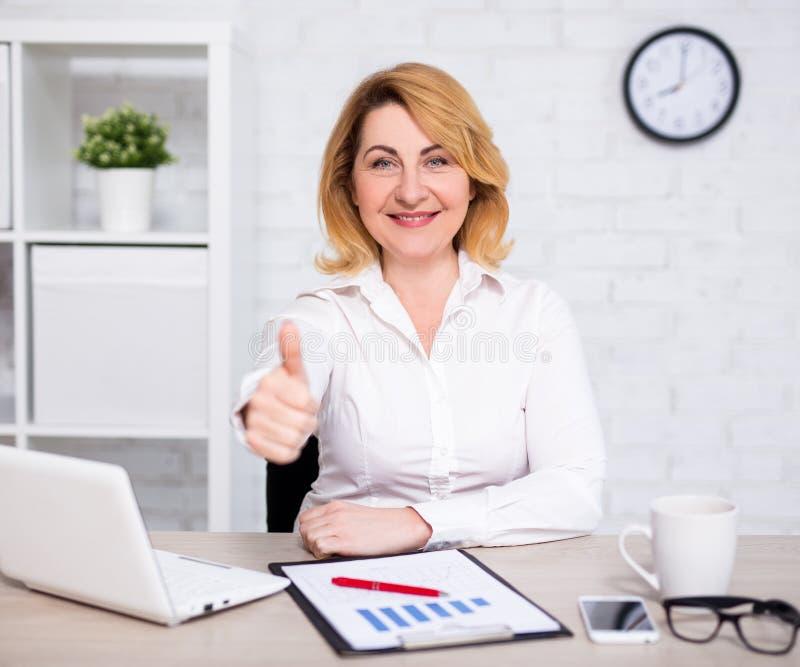 Bedrijfs en succesconcept - gelukkige rijpe bedrijfsvrouwenduimen omhoog in bureau stock afbeelding