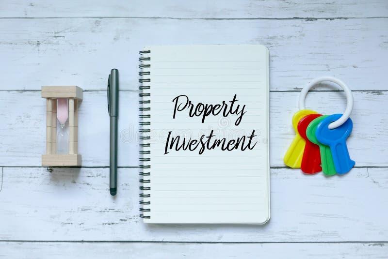 Bedrijfs, financiën en bezitsconcept Hoogste mening van zandklok, pen, sleutels en notitieboekje dat met Bezitsinvestering wordt  stock afbeelding