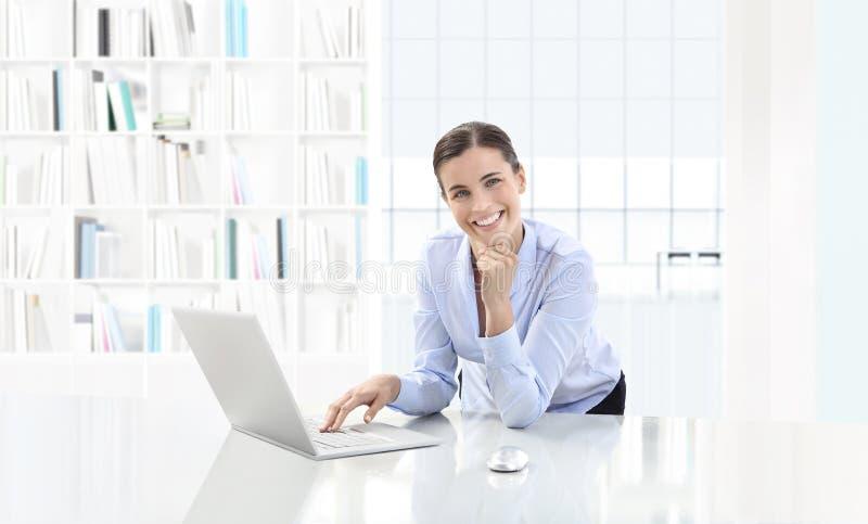 Bedrijfs glimlachende vrouw of een bediende die bij haar bureauverstand werken royalty-vrije stock afbeeldingen