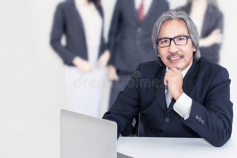 Bedrijfs hogere oude mens ernstig in bureau Hij die het glimlachen kijken stock afbeeldingen