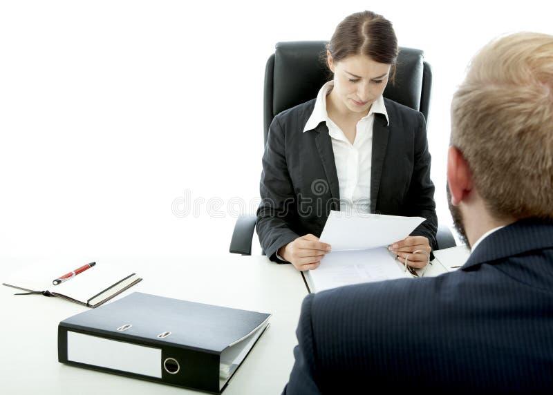Bedrijfs man donkerbruine vrouw bij bureau gelezen contract royalty-vrije stock afbeelding