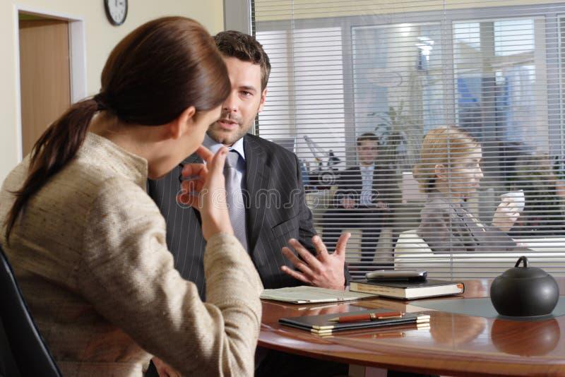 Bedrijfs man en vrouw die in het bureau spreken royalty-vrije stock afbeeldingen