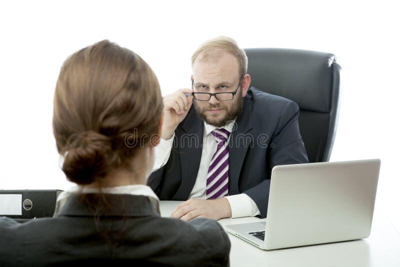 Bedrijfs man vrouw die bij bureau ernstig kijkt stock fotografie
