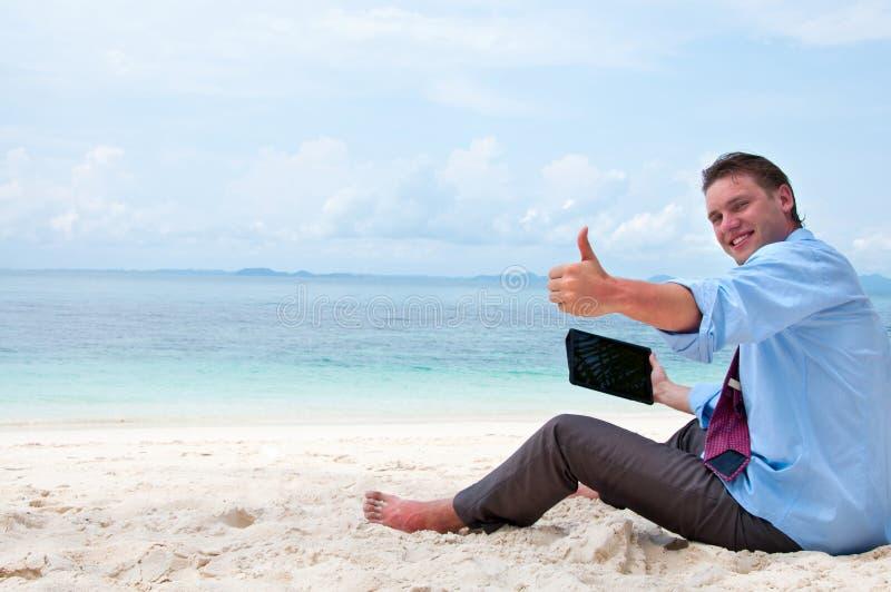 Bedrijfs mens die aan het strand met PC werkt stock foto