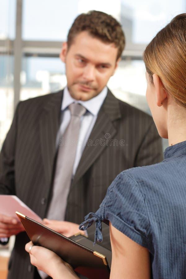 Bedrijfs mens die aan zijn secretaresse in het bureau spreekt stock foto