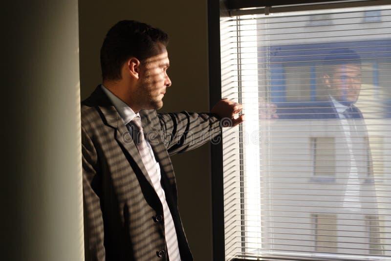 Bedrijfs mens die door vensterzonneblinden kijkt stock fotografie