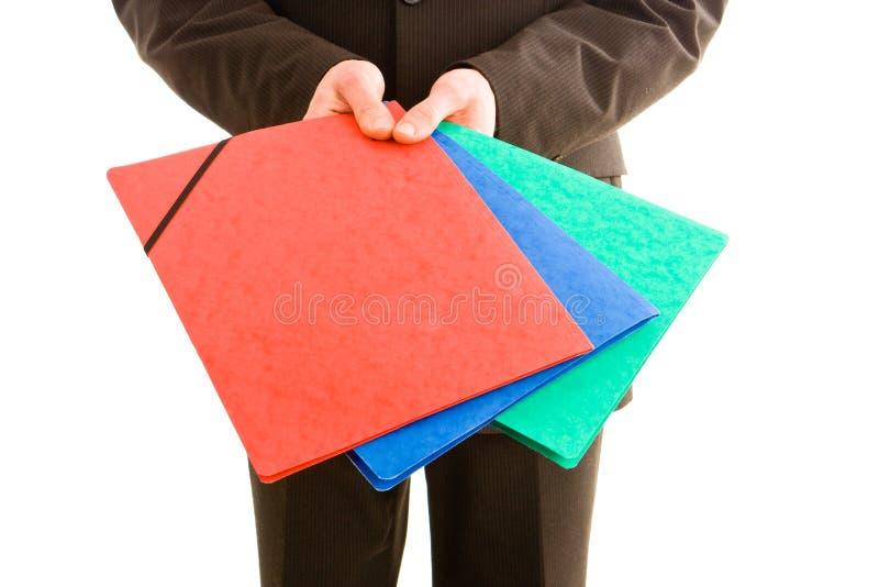 Bedrijfs mens die drie kleurrijke omslagen houdt stock afbeeldingen