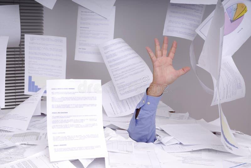 Bedrijfs mens die in een bureauhoogtepunt verdrinkt van documenten stock foto