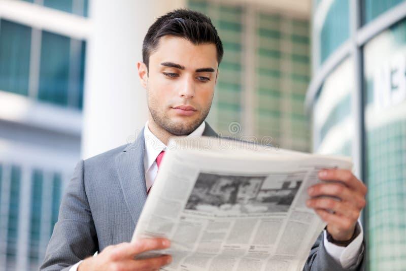 Bedrijfs mens die een krant leest stock afbeelding