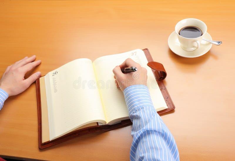 Bedrijfs mens die een nota schrijft bij van hem stock foto's