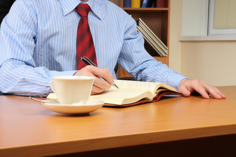Bedrijfs mens die een nota schrijft bij van hem stock afbeeldingen