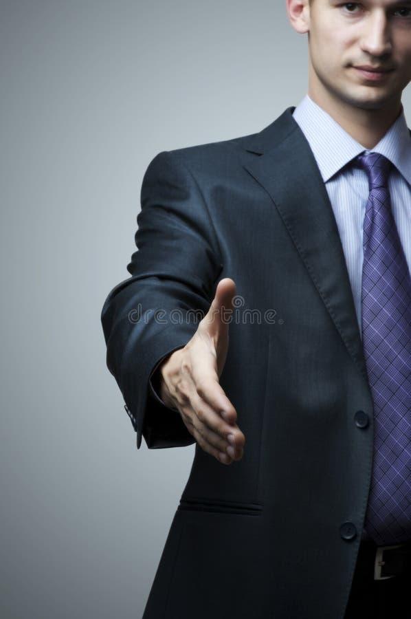 Bedrijfs mens die hand uitbreidt tot schok stock afbeelding