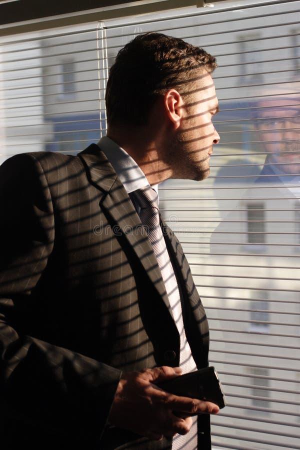 Bedrijfs mens die met telefoon door vensterzonneblinden kijkt royalty-vrije stock fotografie
