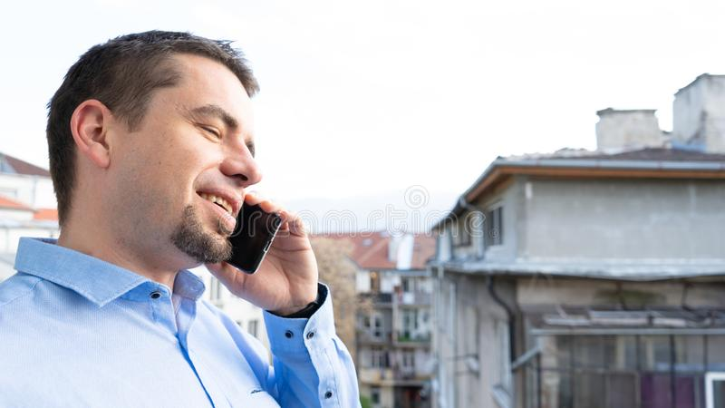 Bedrijfs mens die op telefoon spreekt Jonge kerel die door cellphone te glimlachen roepen stock foto's
