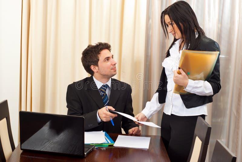 Bedrijfs mens en secretaresse die gesprek hebben royalty-vrije stock afbeeldingen