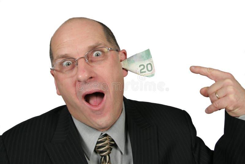 Bedrijfs Mens met Geld dat uit zijn Oren komt stock foto