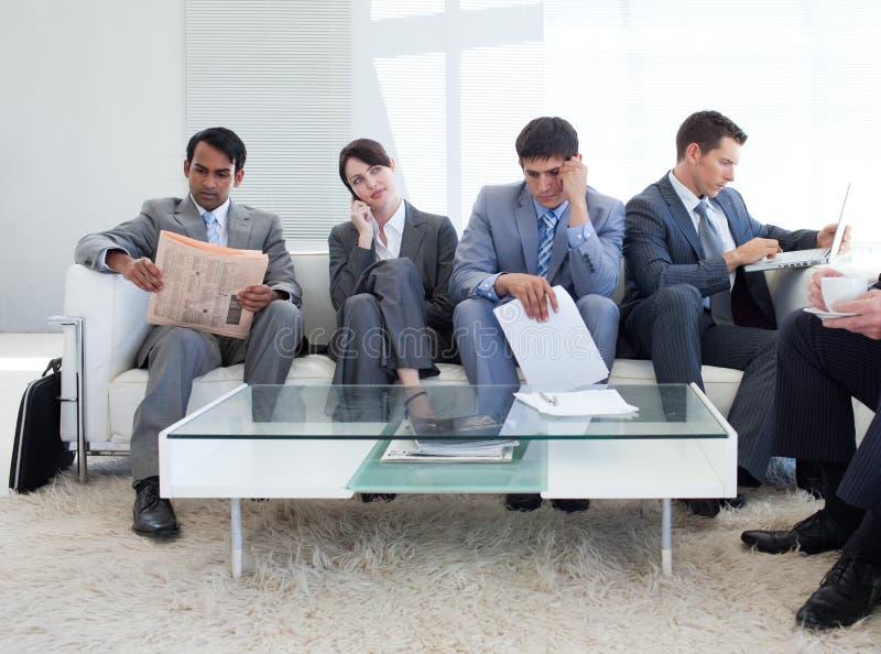 Bedrijfs mensen die in een wachtkamer zitten stock fotografie