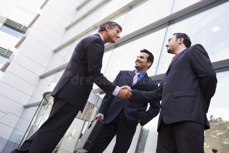 Bedrijfs mensen die handen buiten bureau schudden