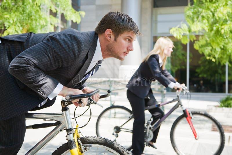 Bedrijfs mensen die op fietsen rennen stock afbeelding