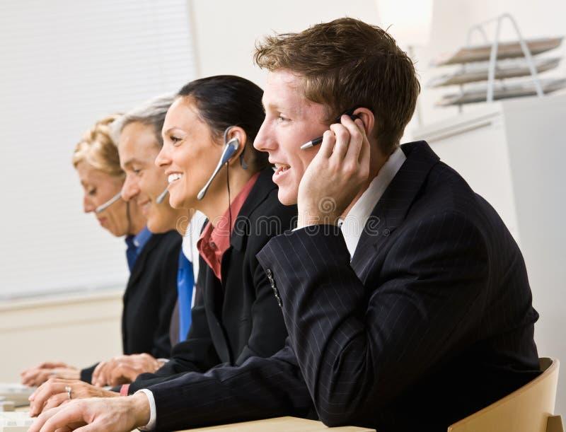 Bedrijfs mensen die op hoofdtelefoons spreken royalty-vrije stock foto's