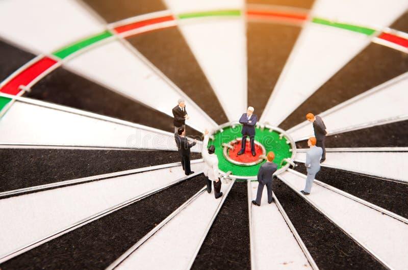Bedrijfs miniatuurmensen die zich op dartboard bevinden stock afbeelding