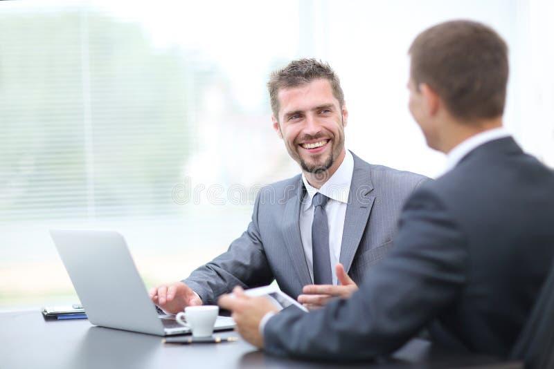 Bedrijfs onderhandelingen Twee collega's die in het bureau spreken royalty-vrije stock afbeeldingen