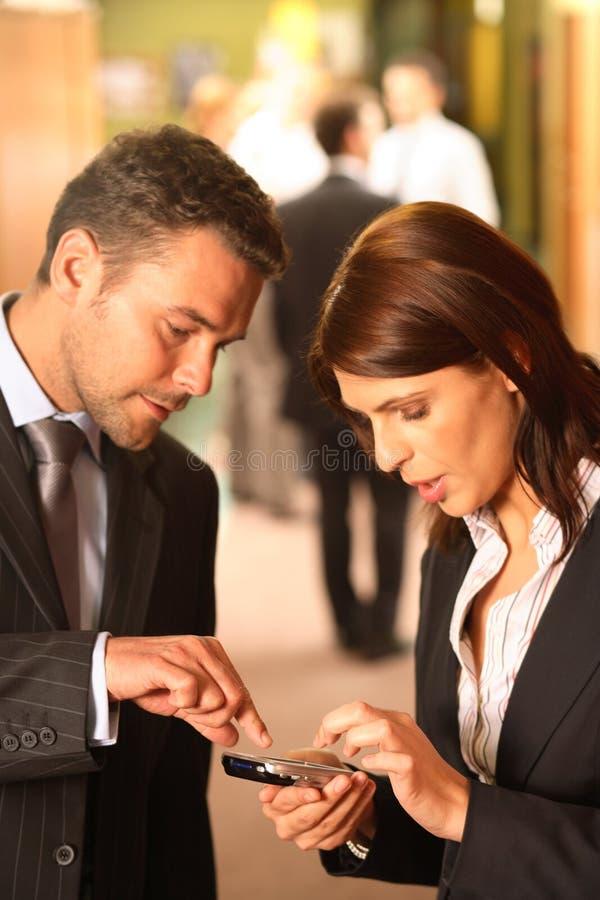Bedrijfs Paar dat Cellphone gebruikt stock afbeelding