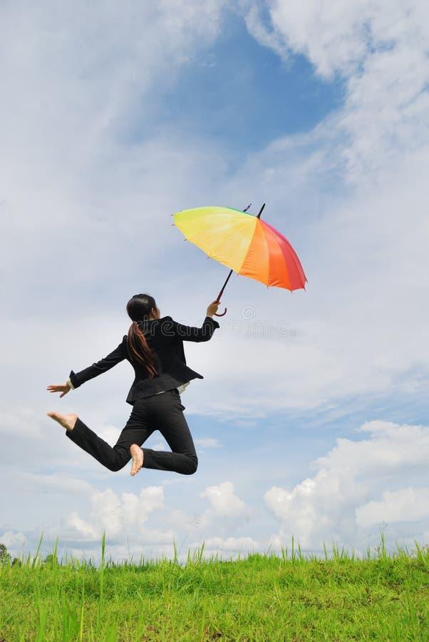 Bedrijfs parapluvrouw die aan blauwe hemel springt royalty-vrije stock foto