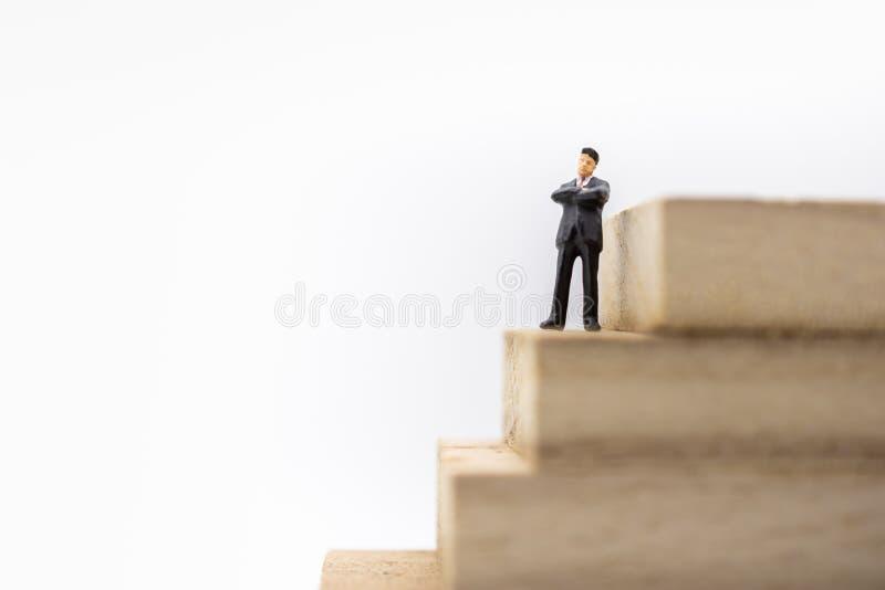 Bedrijfs, Plannings, Successie en Beheersconcept Sluit omhoog van zakenman miniatuurcijfer die en zich op Stapel bevinden denken  stock afbeeldingen