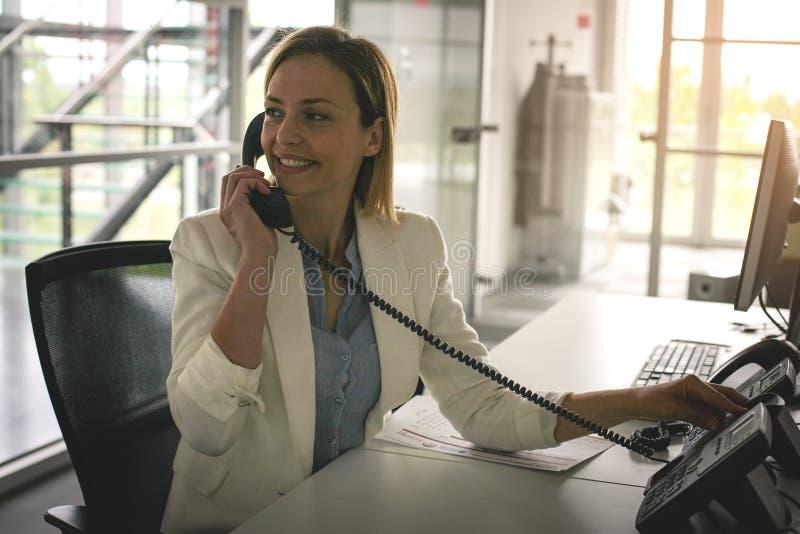 Bedrijfs vrouw die in bureau werkt Vrouw die op Landline spreken phon stock afbeelding