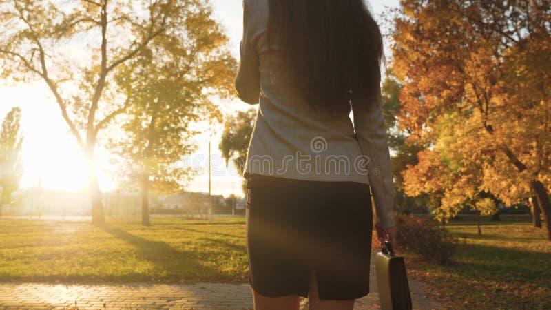 Bedrijfs vrouw die op celtelefoon spreekt vrouwengangen in park in stralen van zonsondergang met zwarte aktentas voor documenten royalty-vrije stock fotografie