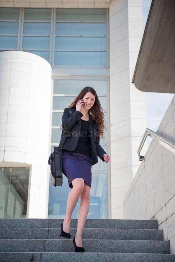 Bedrijfs vrouw die op treden loopt die telefoon roepen stock foto