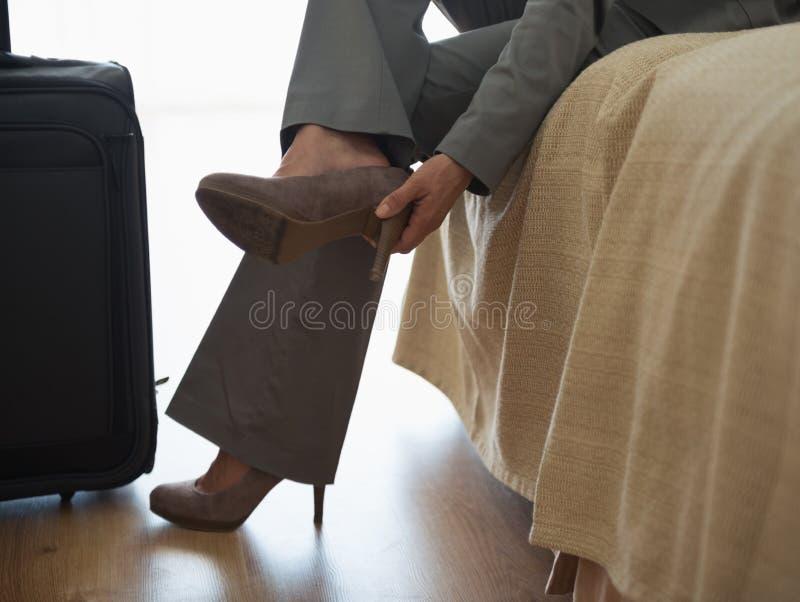 Bedrijfs vrouw die schoenen weg in hotelruimte nemen stock foto