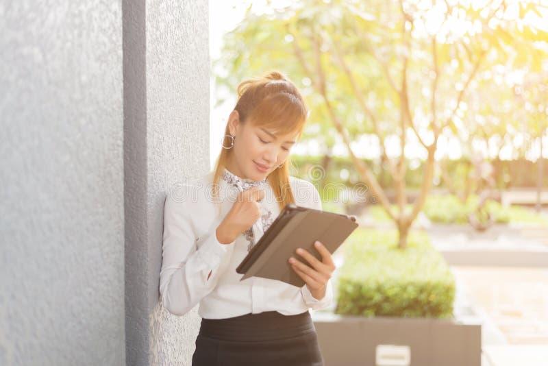 Bedrijfs vrouw die tablet op middagpauze in stadspark gebruikt royalty-vrije stock fotografie