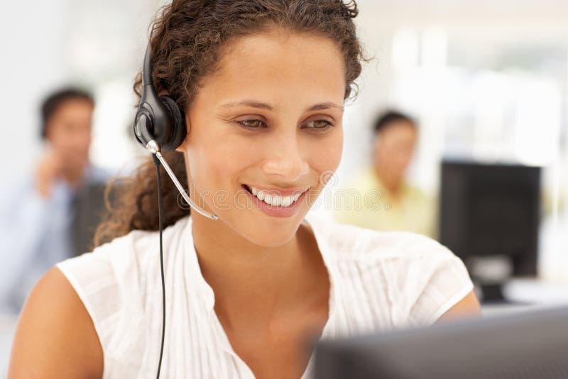 Bedrijfs vrouwen aan het werk dat een hoofdtelefoon met behulp van stock afbeeldingen