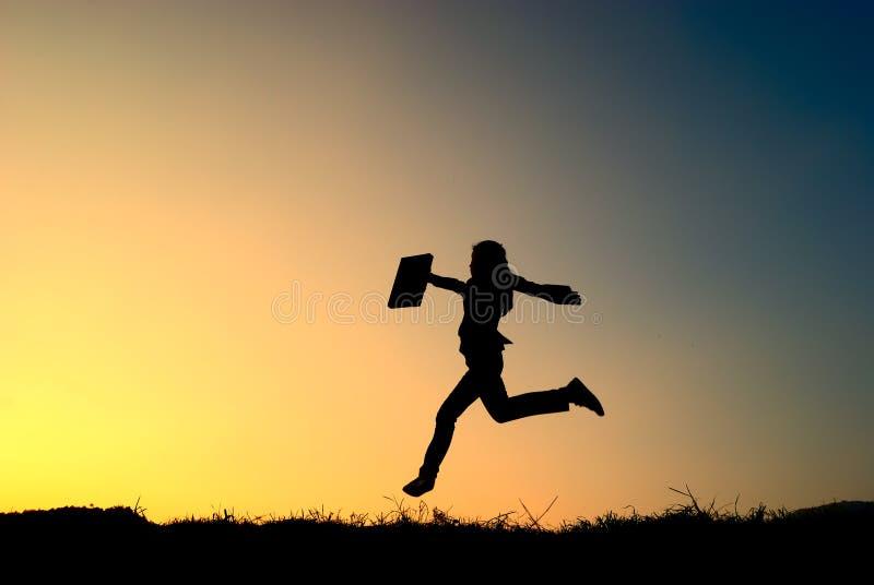 Bedrijfs vrouwen het springen en van de zonsondergang silhouet royalty-vrije stock afbeelding