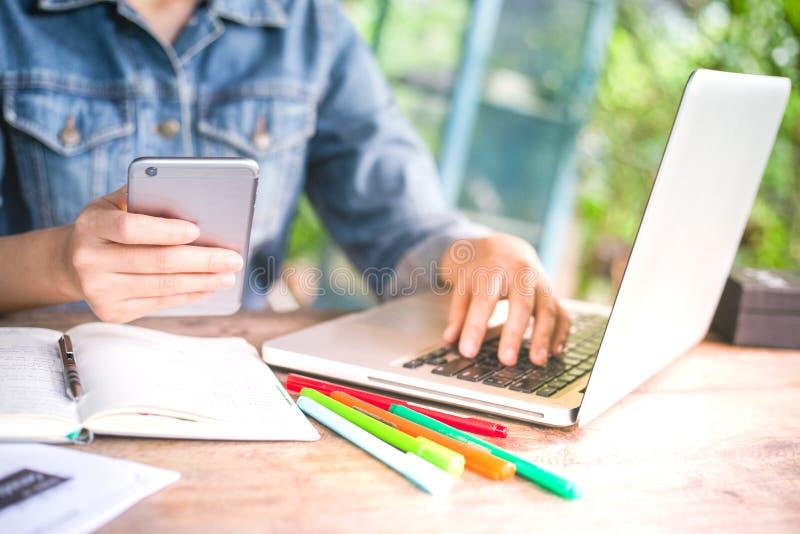 Bedrijfs women's zitting in bureau en het werken van haar computerlaptop aan bureau met het gebruiken van smartphone Vrouw die  stock afbeeldingen