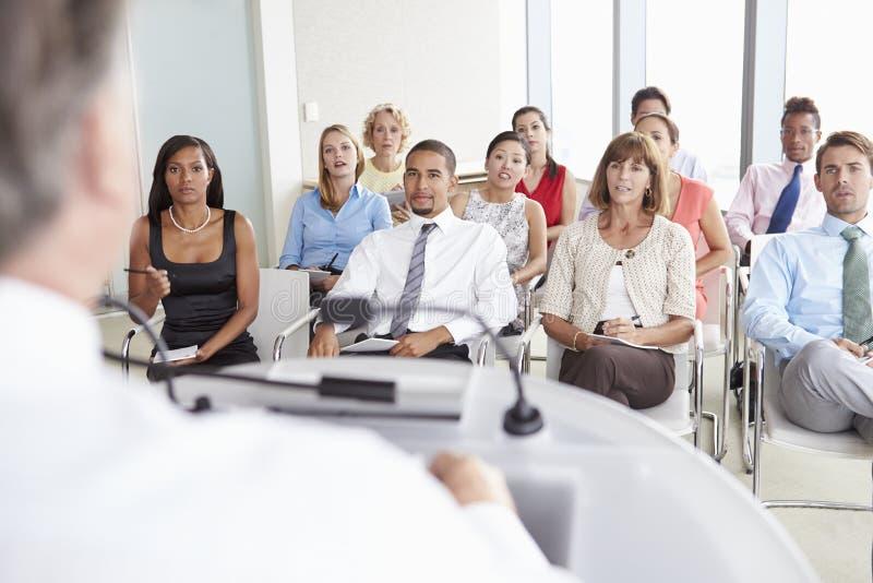 Bedrijfsafgevaardigden die aan Presentatie op Conferentie luisteren royalty-vrije stock foto's