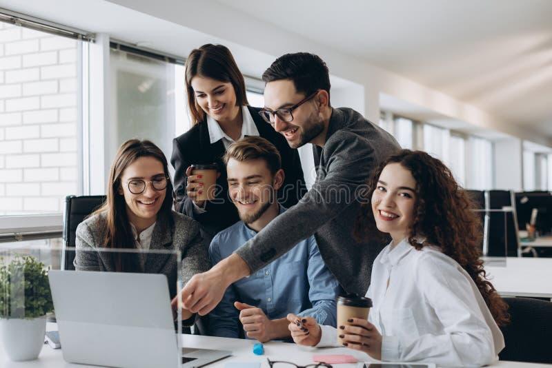 Bedrijfsberoeps Groep jonge zekere bedrijfsmensen die gegevens analyseren die computer met behulp van terwijl het doorbrengen van stock afbeelding