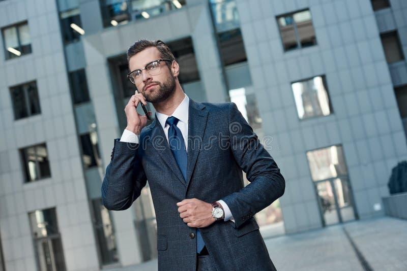 Bedrijfsbespreking Knappe jonge mens in volledig kostuum die op de telefoon spreken Bebouwde mening royalty-vrije stock foto