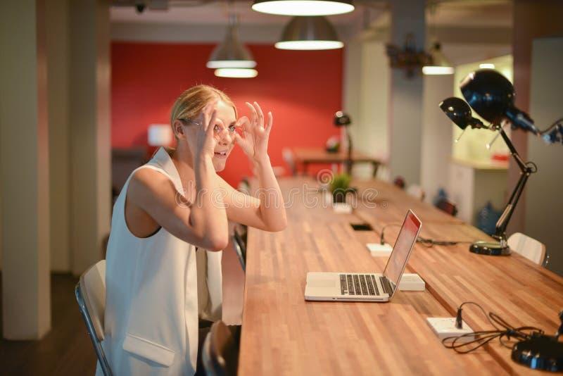 Bedrijfsblondevrouw die een grappige actie in bureau maken royalty-vrije stock afbeeldingen