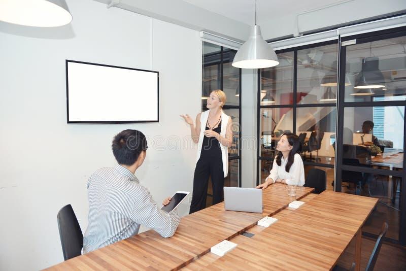 Bedrijfsblondevrouw die een project op lege het schermtv voorleggen stock afbeeldingen