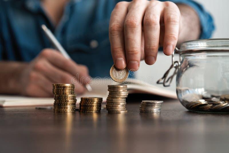 bedrijfsboekhouding met besparingsgeld met hand die muntstukken in financi?le het concept zetten van het kruikglas stock foto's