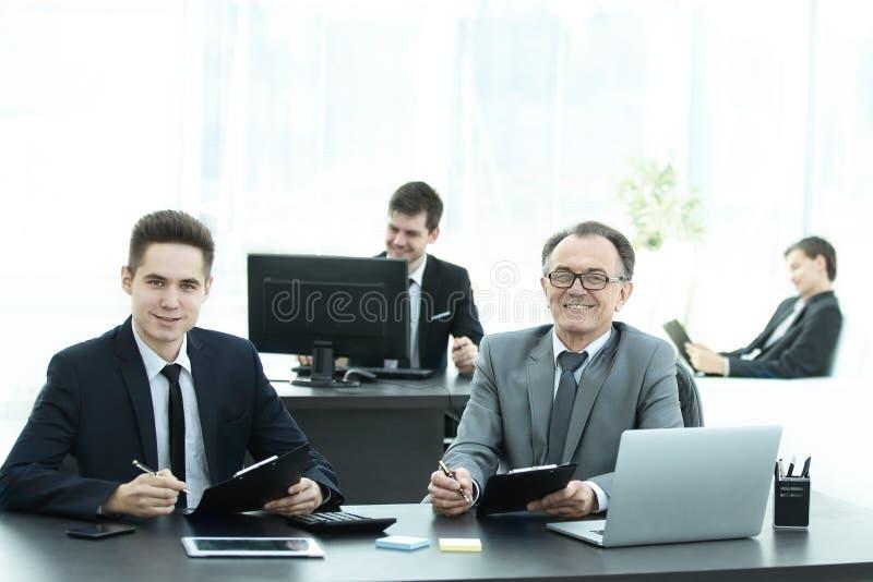 Bedrijfscollega's die bij een Bureau in het bureau zitten royalty-vrije stock afbeelding
