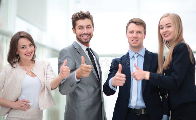Bedrijfscollega's die camera bekijken en duimen omhoog in t stoppen stock foto