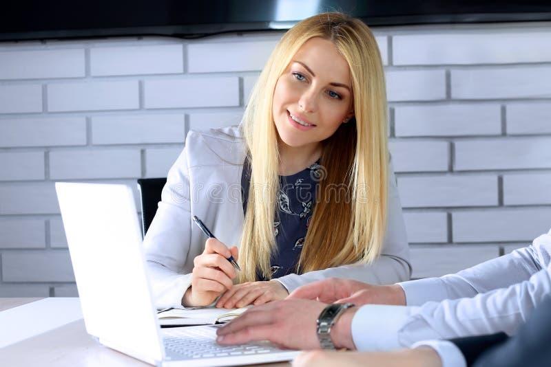 Bedrijfscollega's die en financiële cijfers/grafieken werken analyseren op laptop royalty-vrije stock fotografie