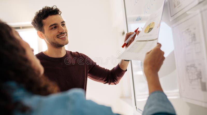 Bedrijfscollega's die het werk aangaande een whiteboard in bureau bespreken royalty-vrije stock foto's